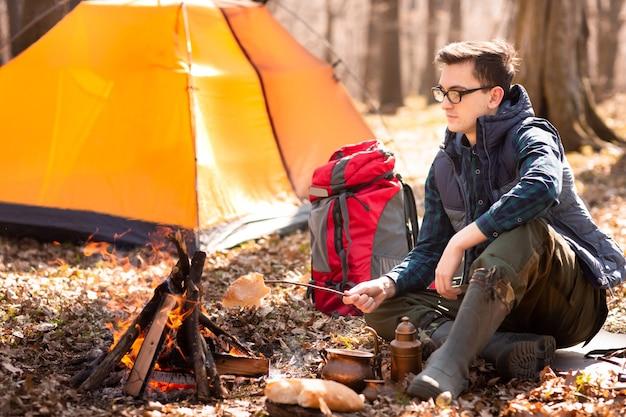 Um jovem viajante na floresta está descansando perto da tenda e café da manhã na natureza