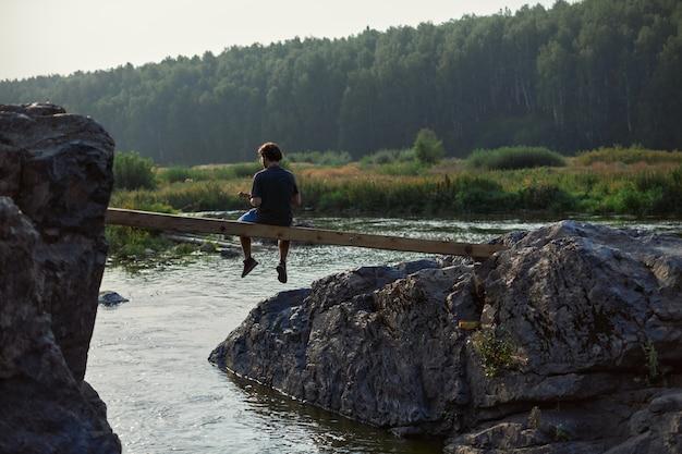 Um jovem viajante senta-se sozinho em uma ponte de madeira entre as rochas e olha para longe ...