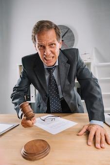 Um juiz maduro com raiva, batendo o martelo na mesa na sala de audiências