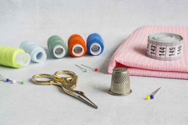 Um kit de costura com pequenas tesouras, bobinas, alfinetes de dedal e fita métrica