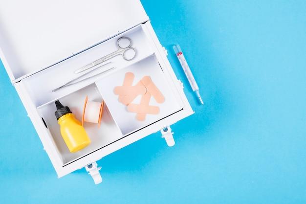 Um kit de primeiros socorros aberto com seringa no fundo azul