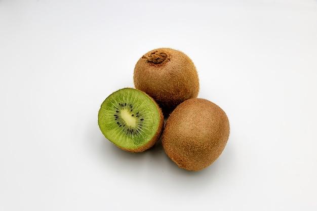 Um kiwi fatiado e dois kiwi inteiro em um papel branco
