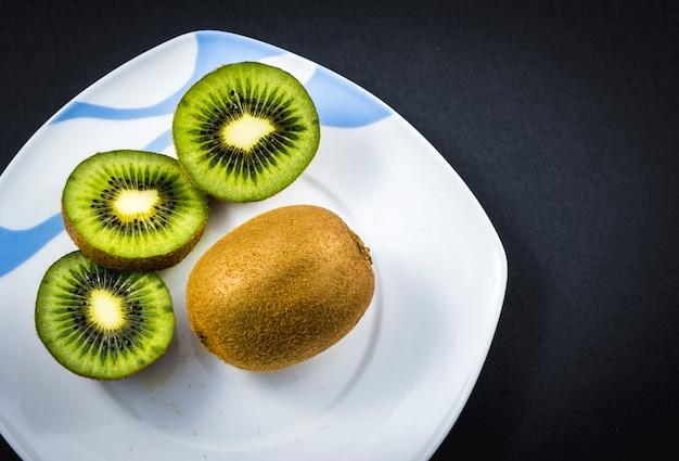 Um kiwi inteiro e dois kiwis cortados em um prato branco no preto