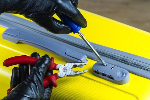 Um ladrão, um fraudador está tentando arrombar, abre uma fechadura combinada em uma mala. conceito de roubo