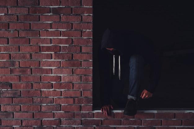 Um ladrão vestido de escuro e com um casaco de couro quebra a janela de uma residência.