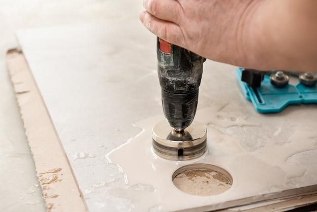 Um ladrilhador está usando uma coroa de diamante para fazer furos no ladrilho de cerâmica de perto