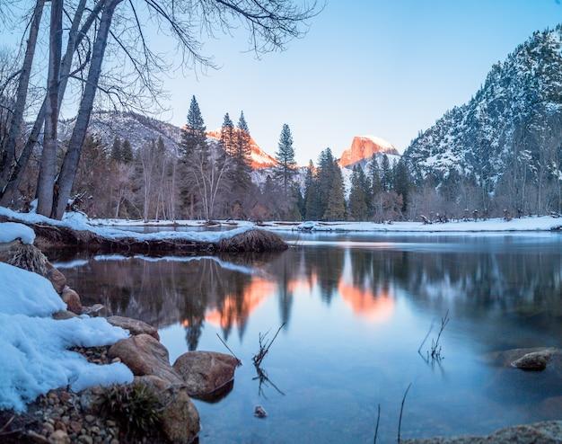 Um lago cercado por rochas, árvores e montanhas em yosemite durante o inverno