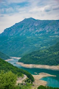 Um lago de montanha incomum com águas azul-turquesa está localizado em um desfiladeiro entre as altas montanhas.