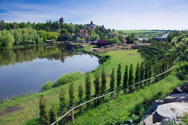 Um lago no meio de um jardim verde com floresta e residência