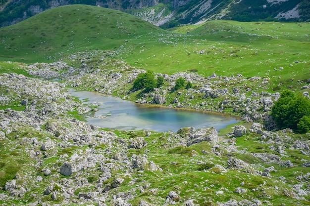 Um lago pequeno da montanha entre as montanhas pitorescas altas.