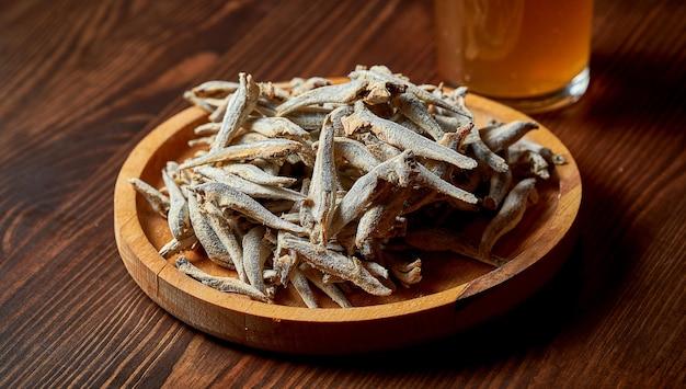 Um lanche clássico de cerveja - anchovas secas e salgadas em um suporte de madeira. pub de comida