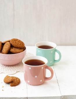 Um lanche saboroso: duas xícaras de chá e uma tigela de biscoitos.