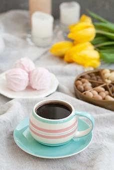 Um lanche saboroso: uma xícara de café, um prato de zéfiro e uma caixa de doces.