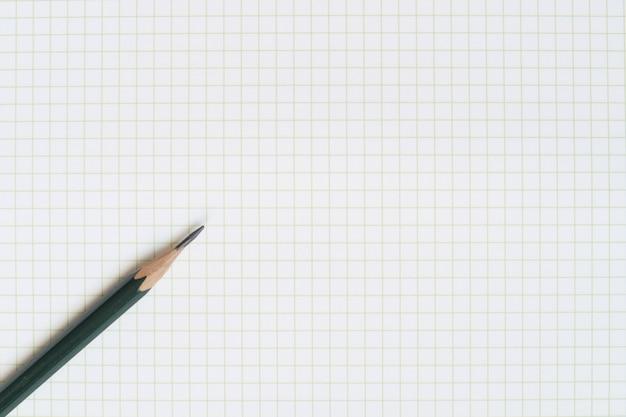 Um lápis de madeira verde e um papel de nota pegajoso no papel em branco da grade.