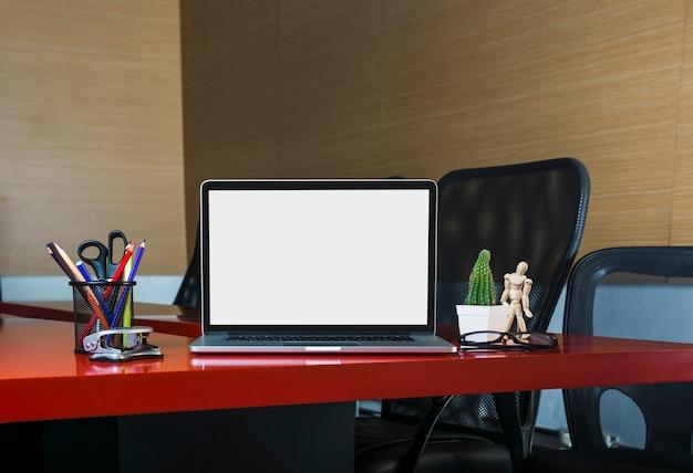 Um laptop aberto com artigos de papelaria na mesa de escritório no escritório