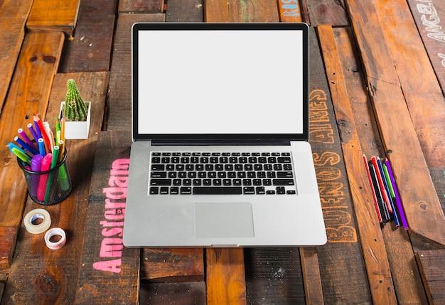 Um laptop aberto com artigos de papelaria na mesa de madeira do escritório