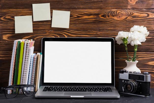 Um laptop aberto com tela branca em branco; câmera vintage; óculos e livros na mesa de madeira