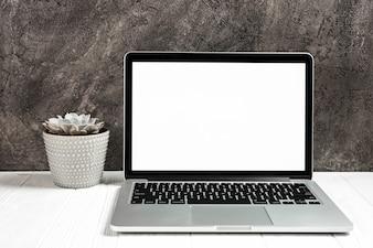 Um laptop aberto com tela branca em branco na mesa de madeira contra a parede preta