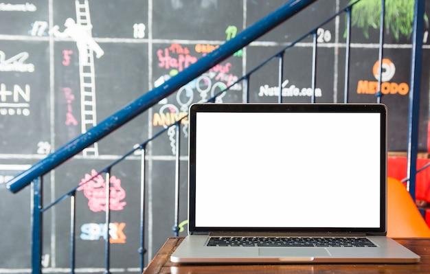 Um laptop aberto com tela branca na mesa