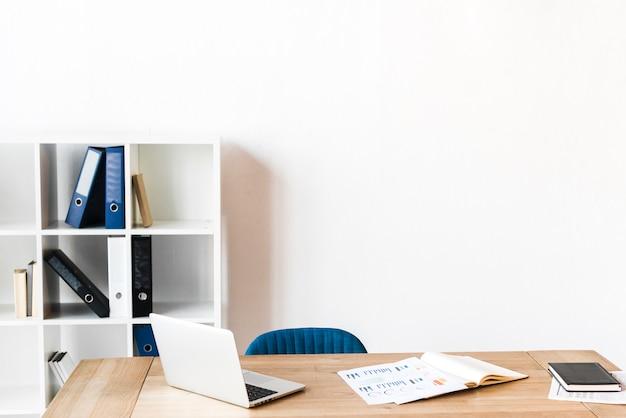 Um laptop aberto e gráfico na mesa de madeira no escritório
