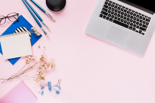 Um laptop aberto; flores e artigos de papelaria no fundo rosa