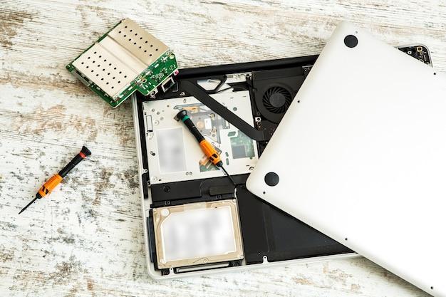 Um laptop aberto sendo consertado.