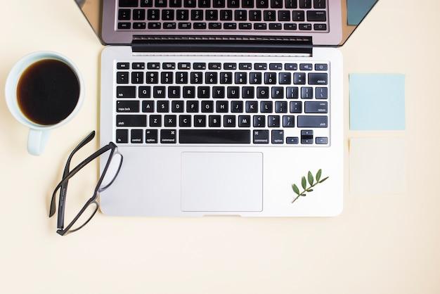 Um laptop aberto; xícara de chá; óculos e bloco de notas em fundo bege