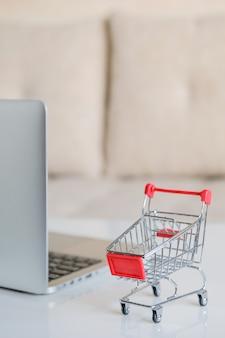 Um laptop cinza sobre uma mesa ao lado de um carrinho de compras de um supermercado. vertical.