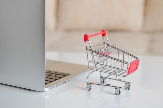 Um laptop cinza sobre uma mesa ao lado de um carrinho de compras de um supermercado.