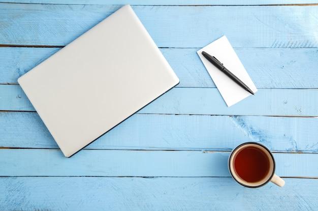 Um laptop cinza, um copo de bebida, um pequeno caderno de papel e uma caneta preta em uma madeira azul