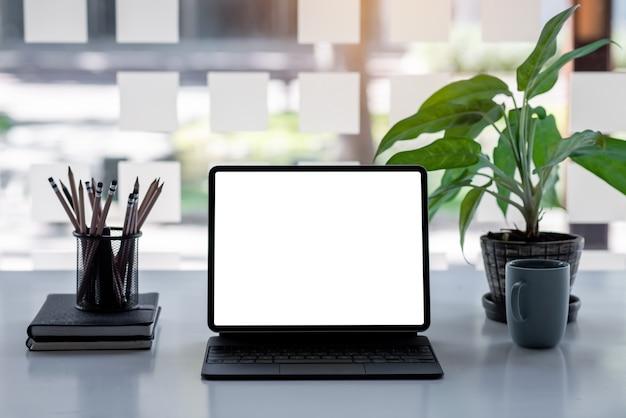 Um laptop de tela branca com um teclado preto sobre a mesa e árvores verdes.