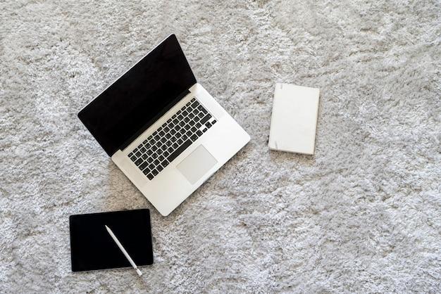 Um laptop e outros dispositivos no chão no carpete macio da sala de casa, isolamento durante a pandemia de coronavírus