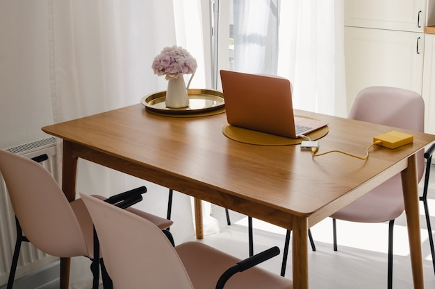Um laptop e uma jarra com flores na mesa de jantar de madeira da cozinha em um dia ensolarado