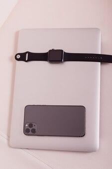 Um laptop, um relógio e um telefone estão em um lindo sofá branco