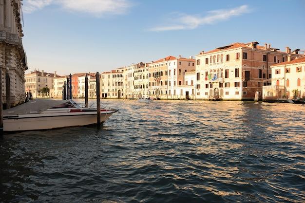 Um largo canal na veneza italiana entre edifícios antigos, iluminados pelo sol, com barcos nele.