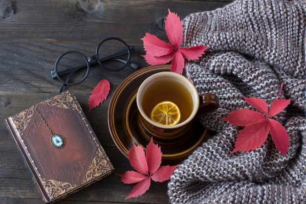 Um lenço, folhas de outono, uma xícara de chá com limão, um livro, óculos