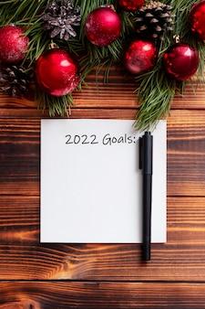 Um lençol branco com o título 2022 gols e um marcador preto em uma mesa de madeira. decorações de ano novo