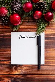 Um lençol branco com o título querido papai noel, um marcador preto em uma mesa de madeira, decorações de ano novo