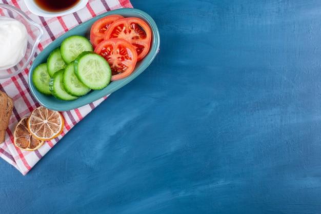 Um leve café da manhã em uma toalha de chá no azul.