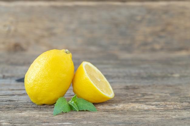 Um limão inteiro e meio com uma folha de hortelã na madeira