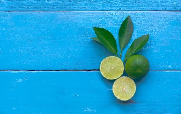 Um limão limão é meio cortado em fundo azul de madeira