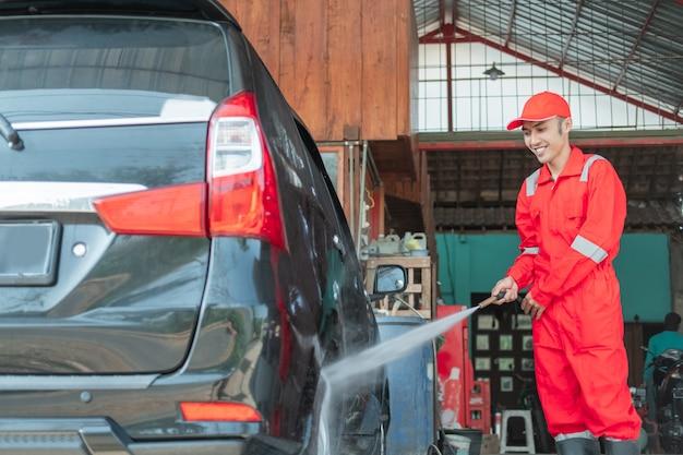 Um limpador de carro usando um uniforme vermelho borrifa água de alta pressão usando uma mangueira nos pneus no lava-rápido