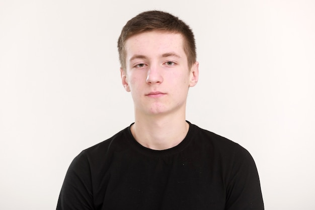 Um lindo adolescente com uma cara séria e triste, cabelo escuro e uma camiseta preta com as mãos postas sobre um fundo branco. mock up, modelo para impressão de design.