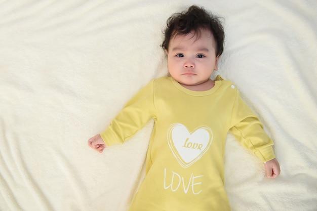 Um lindo bebê asiático com um vestido amarelo está deitado na cama branca olhando para a câmera e fazendo uma expressão triste