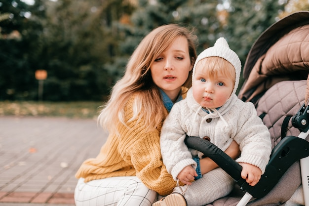 Um lindo bebê em um carrinho fora no outono com sua adorável mãe feliz.