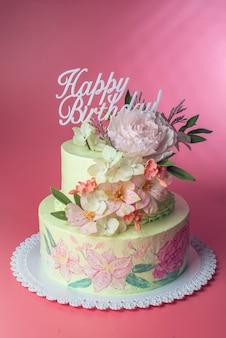 Um lindo bolo de duas camadas na primavera, decorado com rosas da parte superior da mástique e textos em cima do feliz aniversário