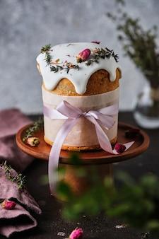 Um lindo bolo de páscoa decorado com flores, ervas e fitas.