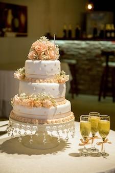 Um lindo bolo de três camadas com enfeites de rosas e taças de champanhe na mesa