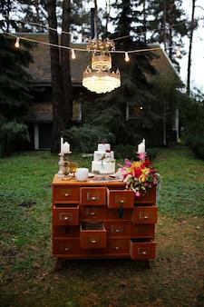 Um lindo bolo de três camadas de casamento decorado com pássaros, flores cor de rosa e galhos com folhas verdes em estilo rústico. sobremesa festiva. conceito de casamento.