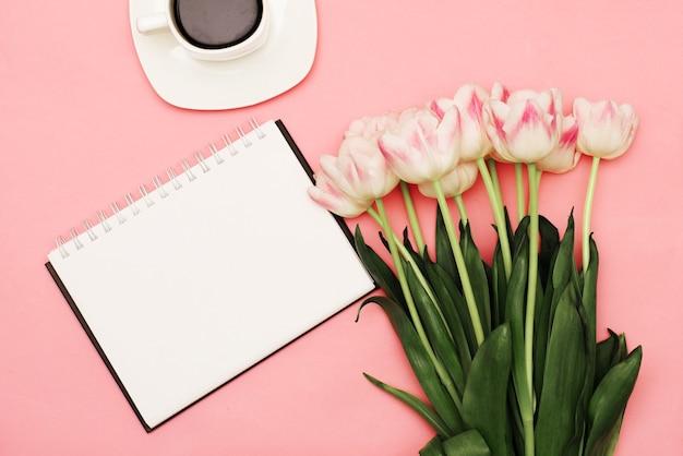 Um lindo buquê de delicadas tulipas cor de rosa ao lado de uma xícara de café em um fundo rosa com um lugar para seu texto em um fundo branco